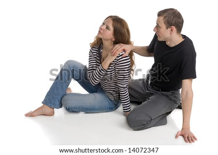 young man and beautiful woman sitting together on white floor background