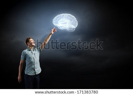 Young man and brain illustration against dark background