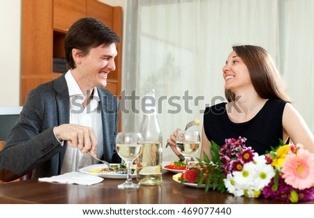 Young man and cute woman having romantic dinner in home