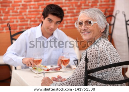 Young man and elderly woman in a restaurant - stock photo