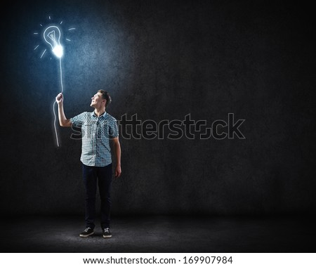 Young man and electrical bulb against dark background - stock photo