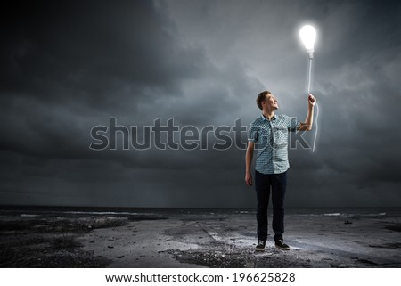Young man and electrical bulb against dark background