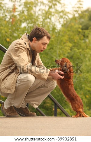 Young man and his adorable dachshund  outdoor - stock photo
