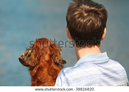 Young man and his dachshund  from back outdoor against water