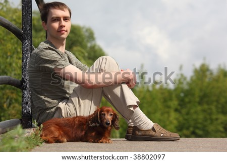 young man and his dachshund sits outdoor in summer - stock photo