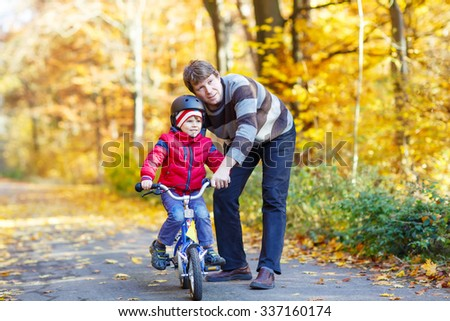 Young man and his little son, kid boy in autumn forest with a bicycle. Father teaching biking. Active family leisure. Child with helmet. Safety, sports, leisure with kids concept. - stock photo