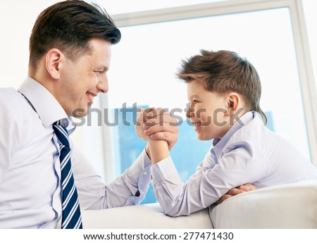 Young man and his son armwrestling - stock photo