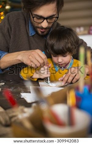 Young man and his son painting xmas decorations with white gouache