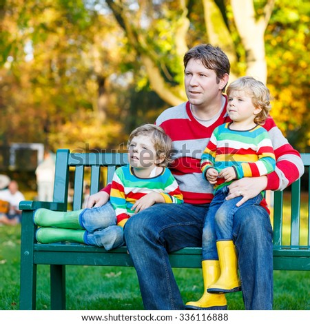 Young man and his two little blond sons sitting together in colorful clothing. Happy kid boys and their dad having fun in autumn park on warm day. - stock photo