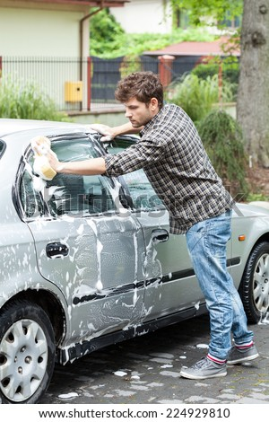 Young man and home car wash in the backyard - stock photo