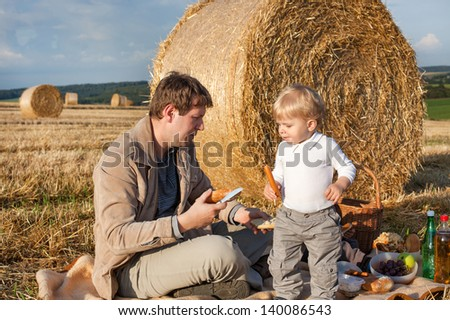 Young man and little toddler boy making evening picnic on hay field, Germany.
