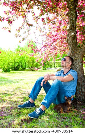 Young man and small dog having rest under blossoming pink cherry tree in green spring park. Multicolored vibrant vertical outdoors image. - stock photo
