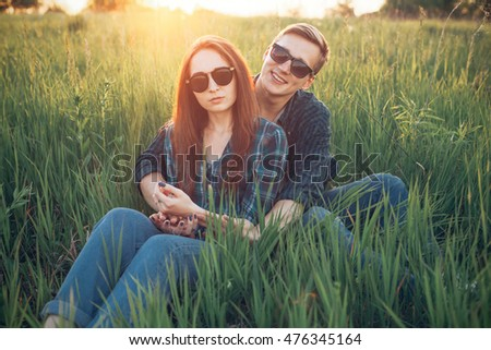 Young man and the girl sitting on the grass and smiling at sunset