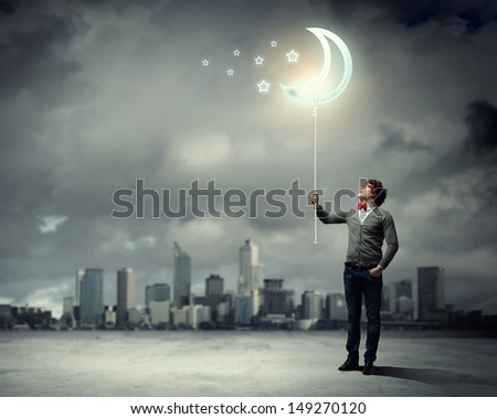 Young man and the moon symbol against polluted and ruined landscape - stock photo