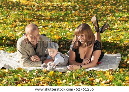 Young man and the woman play with the child in park a grass - stock photo