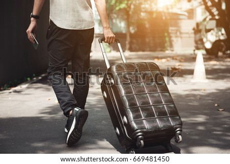 Young man and traveling luggage suitcase walking