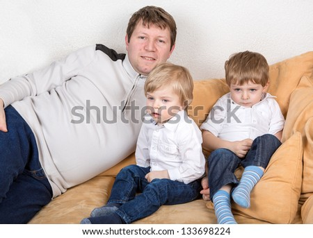 Young man and two beautiful little sons having fun at home. In blue jeans and white shirts. - stock photo