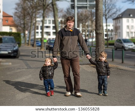 Young man and two little boys walking through spring city, Germany