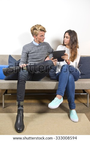Young man and woamn, sitting on a couch in a living room, surfing together on a tablet. The woman is showing him something online. - stock photo