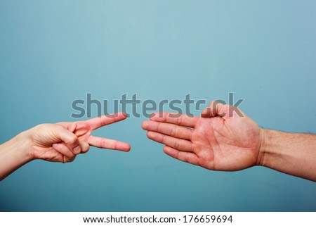 Young man and woman are playing rock paper scissors - stock photo