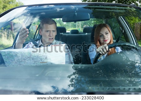 Young man and woman arguing over travel directions - stock photo