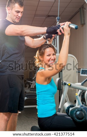 young man and woman at the gym doing exercise - stock photo