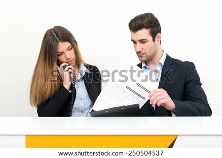 Young man and woman at work as receptionist in hospital talking on the phone for appointment.