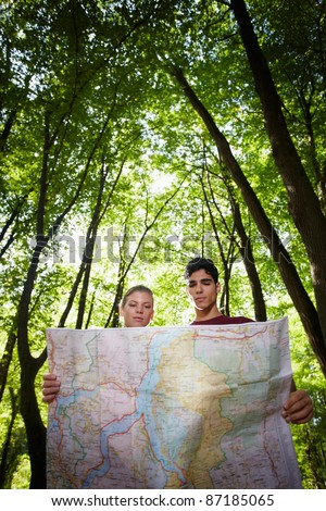young man and woman checking map during hiking excursion and look for destination. Vertical shape, low angle view - stock photo