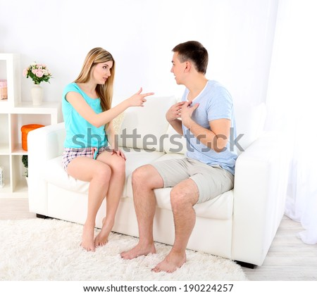 Young man and woman  conflict sitting on sofa argue unhappy, on home interior background