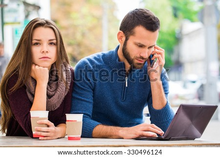 Young man and woman couple in love, man looking at laptop and talking on the phone , the woman looks at us - stock photo
