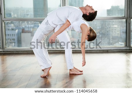 Young man and woman doing stretching fitness exercise at gym - stock photo