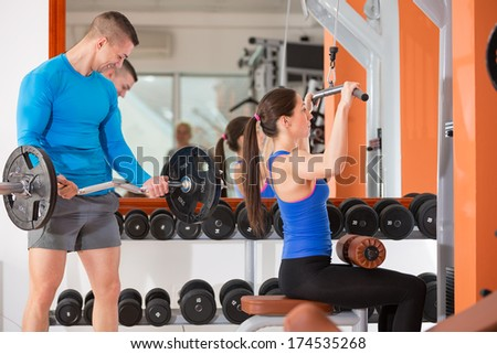 young man and woman doing weight training at gym - stock photo
