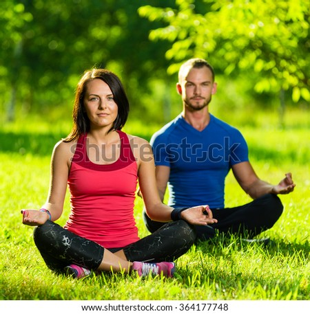 Young man and woman doing yoga in the sunny summer park - stock photo