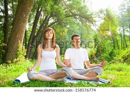 Young man and woman doing yoga. Lotus pose meditation in a garden. Outdoor full body - stock photo
