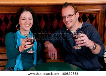 Young man and woman drinking beer in a bar and having fun - stock photo