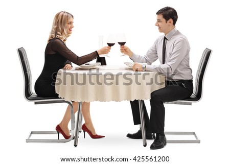 Young man and woman drinking red wine on a romantic date isolated on white background - stock photo