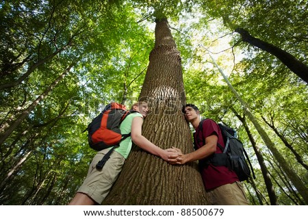 young man and woman during hiking excursion, hugging tree and holding hands. Horizontal shape, low angle view, waist up - stock photo