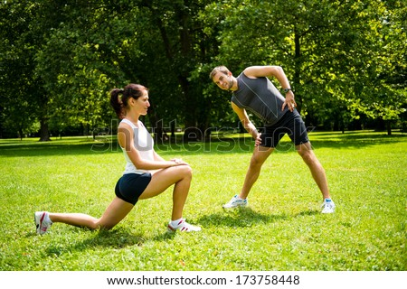 Young man and woman exercising and stretching muscles before sport activity - outdoor in nature