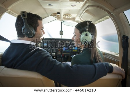 Young man and woman flying in private plane