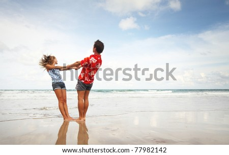 Young man and woman having fun on wet sand at sunny day
