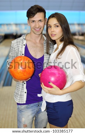 Young man and woman hold orange and pink balls in bowling club; shallow depth of field