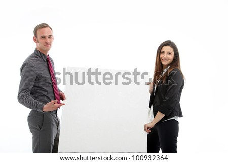 Young man and woman holding a large blank poster Young businessman and businesswoman holding a large blank poster with room to place your message - stock photo