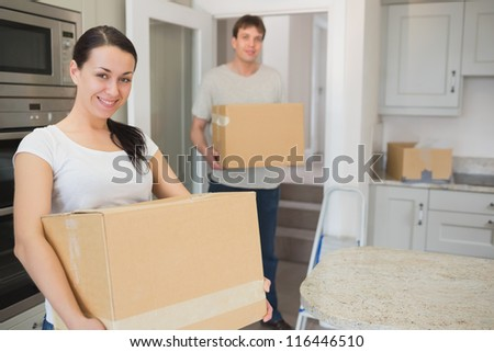 Young man and woman holding boxes in their hands to relocate - stock photo