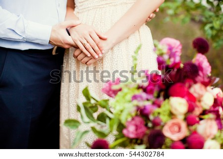 young man and woman holding hands near boho bouquet