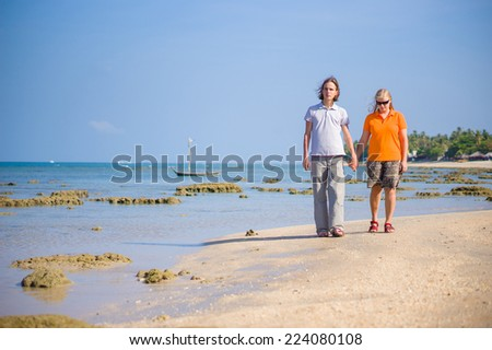 Young man and woman holding hands walk along island beach during low water - stock photo