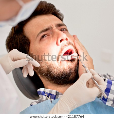 young man and woman in a dental examination at dentist - stock photo