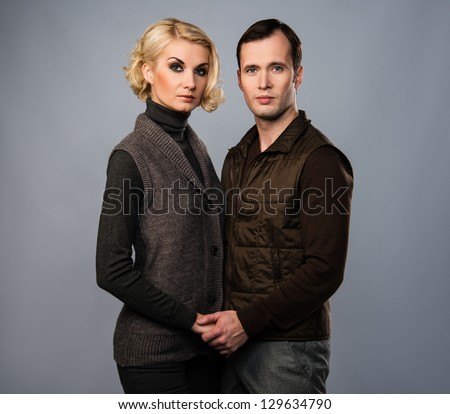 Young man and woman in casual brown wear isolated on grey background - stock photo