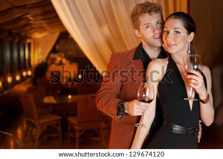 young man and woman in the restaurant for a romantic dinner, focus on woman - stock photo