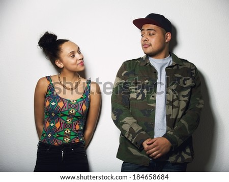 Young man and woman looking at each other with attitude. Young couple in casual wear on grey background. - stock photo