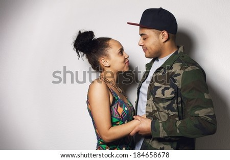 Young man and woman looking at each others eyes. Loving young couple against gray background with copy space - stock photo